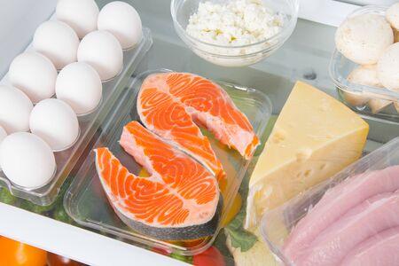primo piano ripiano in frigo dove pesce rosso, uova, formaggio, ricotta, funghi e carne