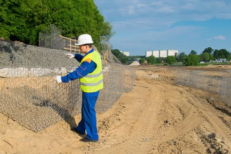 the Builder in a yellow vest and a white helmet, opens a box of mesh to check the design