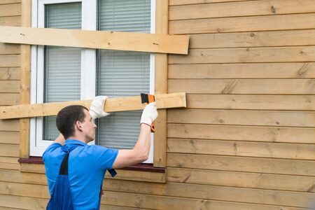 man closes the windows of the house with boards, rear view Reklamní fotografie