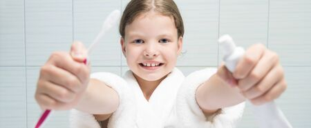 a girl in a white coat holding a toothbrush and toothpaste in her hands, stretching them forward Фото со стока