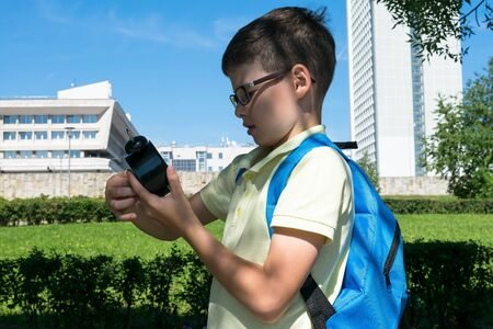 a boy in glasses with a backpack on his back looks at his watch before going to school Фото со стока