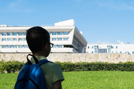 student with a backpack on his back looks at the school building