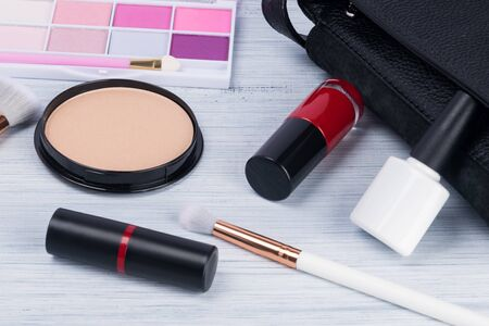 a set of cosmetics from a female little black handbag on a light table