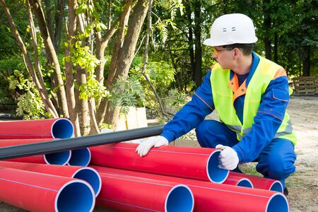 builder checks the condition of red plastic pipes