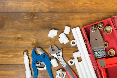a set of objects and tools for assembling water pipes on a wooden background Фото со стока