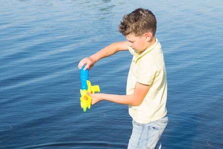 close-up of a boy drawing water into a pistol against the backdrop of a lake to play Фото со стока