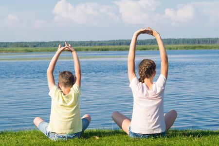 a boy and a girl are sitting on the green grass and doing yoga, holding their hands above their heads, rear view, against the background of a beautiful sky and lake