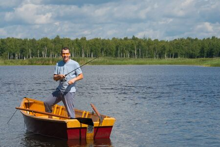 a cheerful man in yellow glasses, in a boat with oars, in the center of the lake, holds a fishing pole to catch a big fish, in the background of a beautiful landscape, there is a place for an inscription Фото со стока