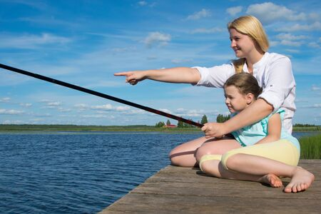 Mom holds the fishing rod and hand shows her daughter on the catch, on the pier, against the backdrop of a beautiful landscape, close-up, there is a place for an inscription