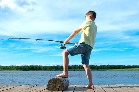 a boy in a yellow t-shirt, on the pier, against the blue lake and the sky,pulls the catch on a fishing rod Stock Photo