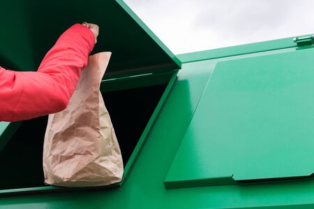 paper bag is thrown into a green garbage container, close-up