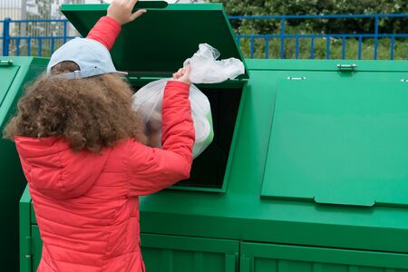 the girl throws the package with waste in the green waste container