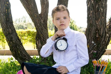 girl in school uniform holding a watch in front of him, back to school