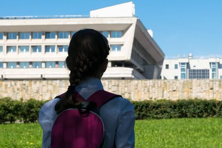 girl in school uniform looking at the school building , rear view
