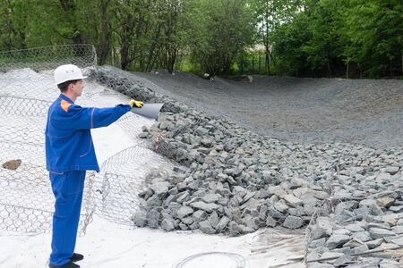 worker in a white helmet at a construction site shows his hand on a stone Фото со стока