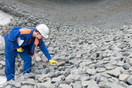 a worker in special clothing checks the quality of stones at a construction site