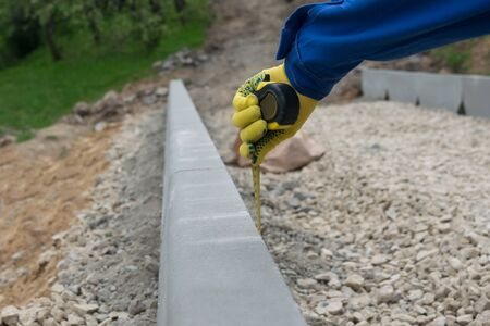 the hand of the employee of the quality department checks the correctness of the roadwork, close-up Фото со стока