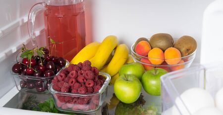 close-up, on the shelf of a white fridge, fresh fruit, berries and a jug with compote Foto de archivo