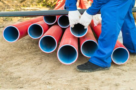 builder works with large plastic pipes, closeup view