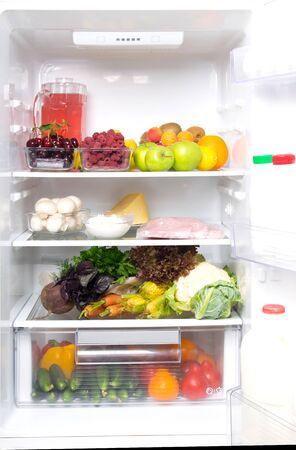 dans un réfrigérateur blanc, sur l'étagère du haut des fruits, des baies et un pot avec de la compote, sur des champignons moyens, de la viande de volaille, du fromage cottage, du fromage, des œufs, sur les légumes du bas et dans la porte des produits laitiers, du kéfir, de la crème Banque d'images