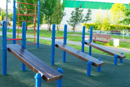 empty exercise machines on the street, a wooden inclined bench press 写真素材