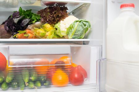 in the White refrigerator on the shelves, fresh vegetables, tomatoes, peppers, carrots, corn, cucumbers, beets, greens, cauliflower, in the door there is milk in the bottle Stock fotó