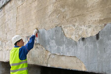 city worker clean walls of graphics and inscriptions, with a metal brush, before painting