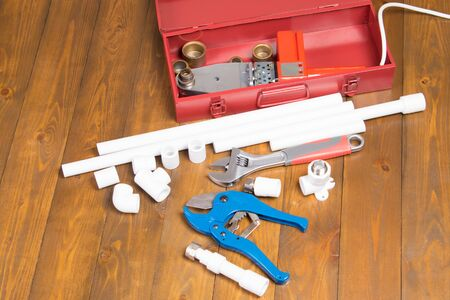polypropylene pipes and soldering tool, in red box, on dark wooden background and blue scissors with key Standard-Bild