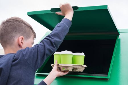boy throws a paper stand with empty cups in the trash tank