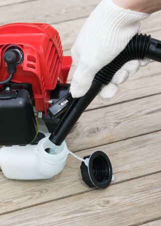 hand in a glove pours gasoline into a tank of a red lawn mower, closeup view