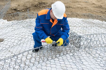 worker in a white helmet and overalls knits a steel wire structure 写真素材 - 129357479