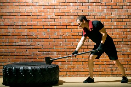 against a brick wall, a man in a black sports uniform, is engaged in cross-fit with a rubber tire and a hammer, there is a place for inscription