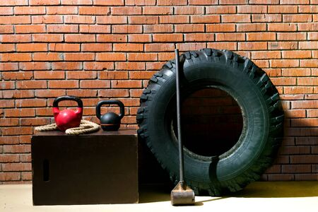 against the background of an orange brick, there are objects for doing cross-fit, a black tire, a hammer, a rope and weights