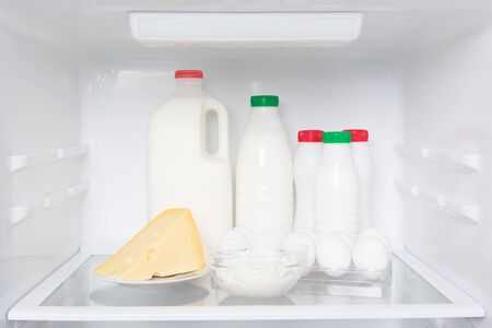 on the shelf of a white refrigerator, stock of products from animal origin, milk, kefir, cream, cheese, eggs and cottage cheese