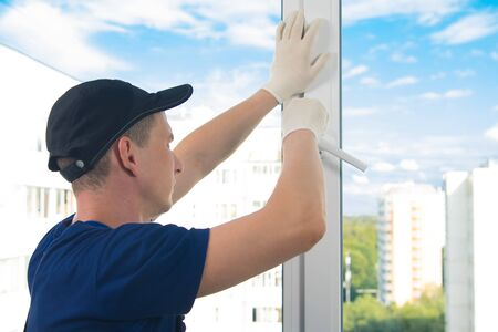 worker in blue uniform adjusts the opening of a plastic window against the sky