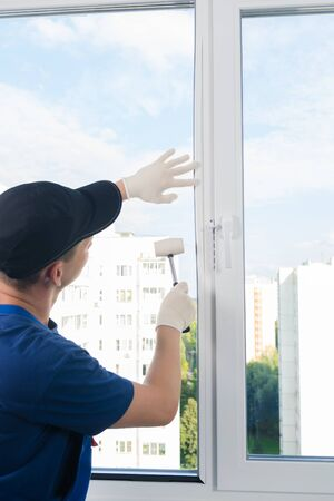 plastic window installation wizard fastens glass with a rubber mallet Stock Photo