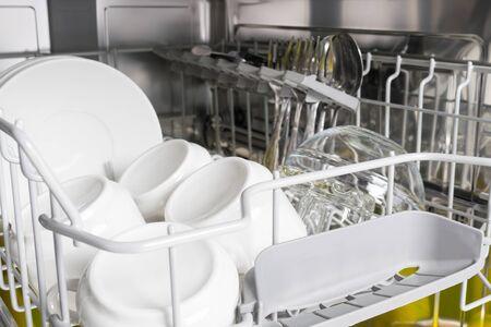 Platos blancos limpios de pie en el lavavajillas, primer plano de fondo
