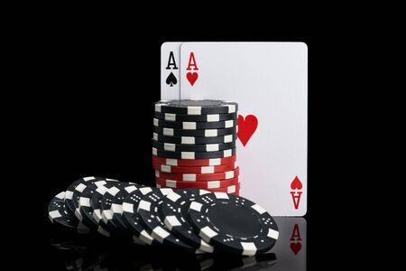 due carte e fiches da poker nere e rosse su sfondo nero Archivio Fotografico