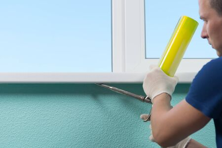 master in white gloves, fulfills the bottom of the window sill foam, for tightness and insulation of the window sill in the house