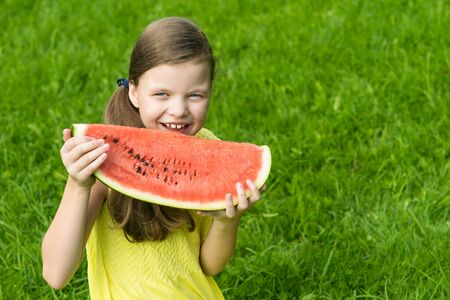 girl holding a big red slice of watermelon in her hands and smiling