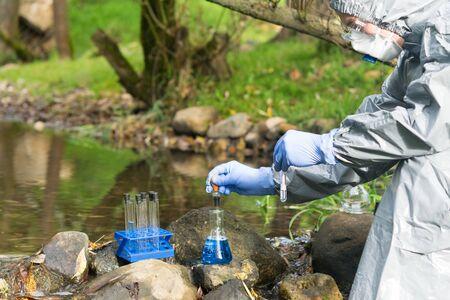 Un hombre con traje protector y respirador analiza el agua del río en un laboratorio portátil utilizando reactivos especiales. Foto de archivo