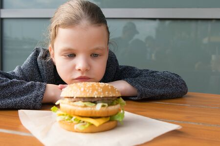 teen girl looking at appetizing Burger lying in front of her on the table Stok Fotoğraf