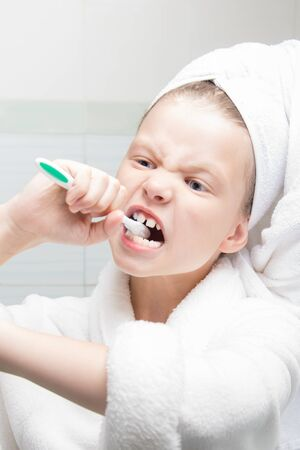 girl in a white coat and with a towel on her head bites a toothbrush