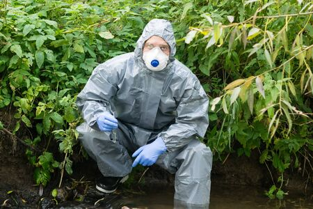 a man in a protective suit against microbes took a sample of water in a flask