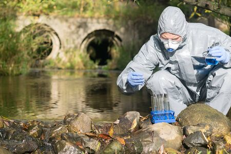 a man in a protective suit does an express test-tube test on the river bank