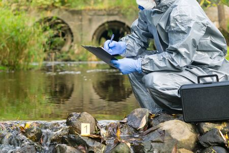 Lab technician in protective suit records environmental analyzes after an environmental disaster