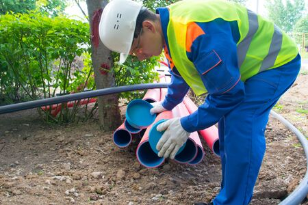 worker in protective uniform, inserts a cap into plastic pipes, to protect from water