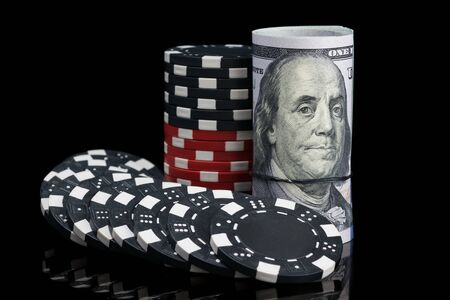 black and white poker chips next to money on a black background 写真素材 - 132242967