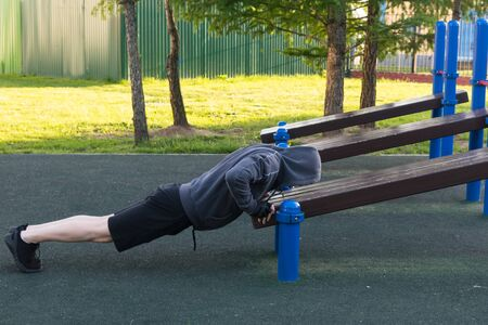 athlete doing pushups on street sports ground in the morning