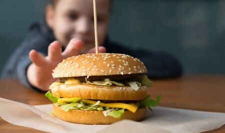children's hand reaches for a big juicy burger